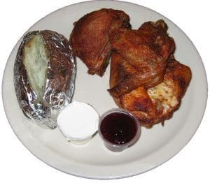 Baked chicken, baked potato and cranberry dinner plate.