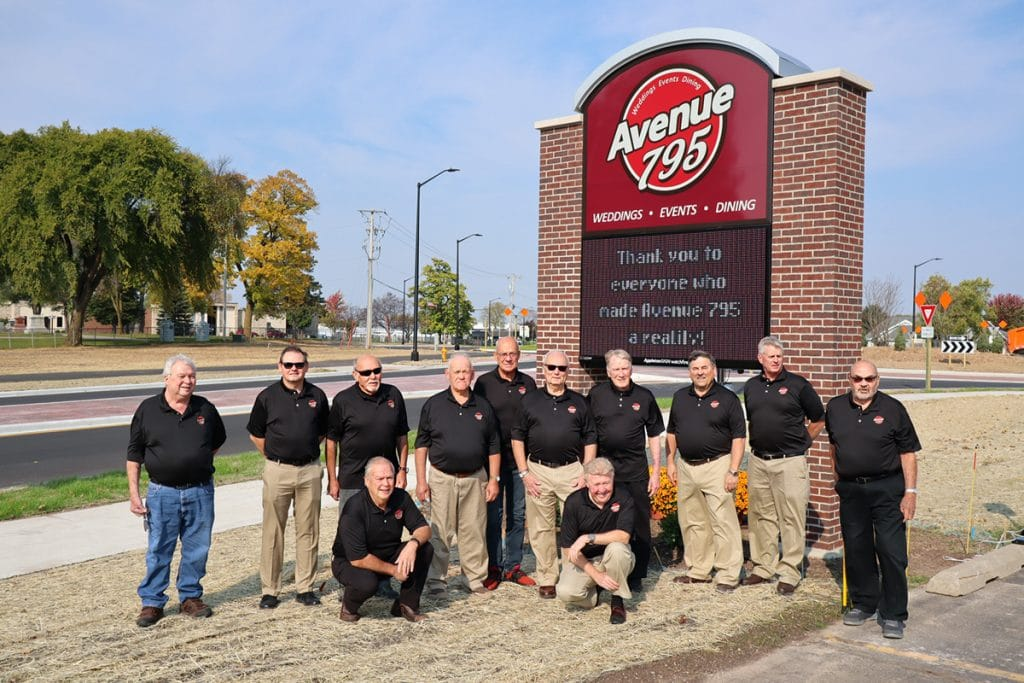 Avenue 795 board members in front of the new sign.